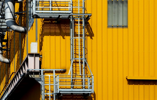 industrial ladders supplier - ladder on yellow building